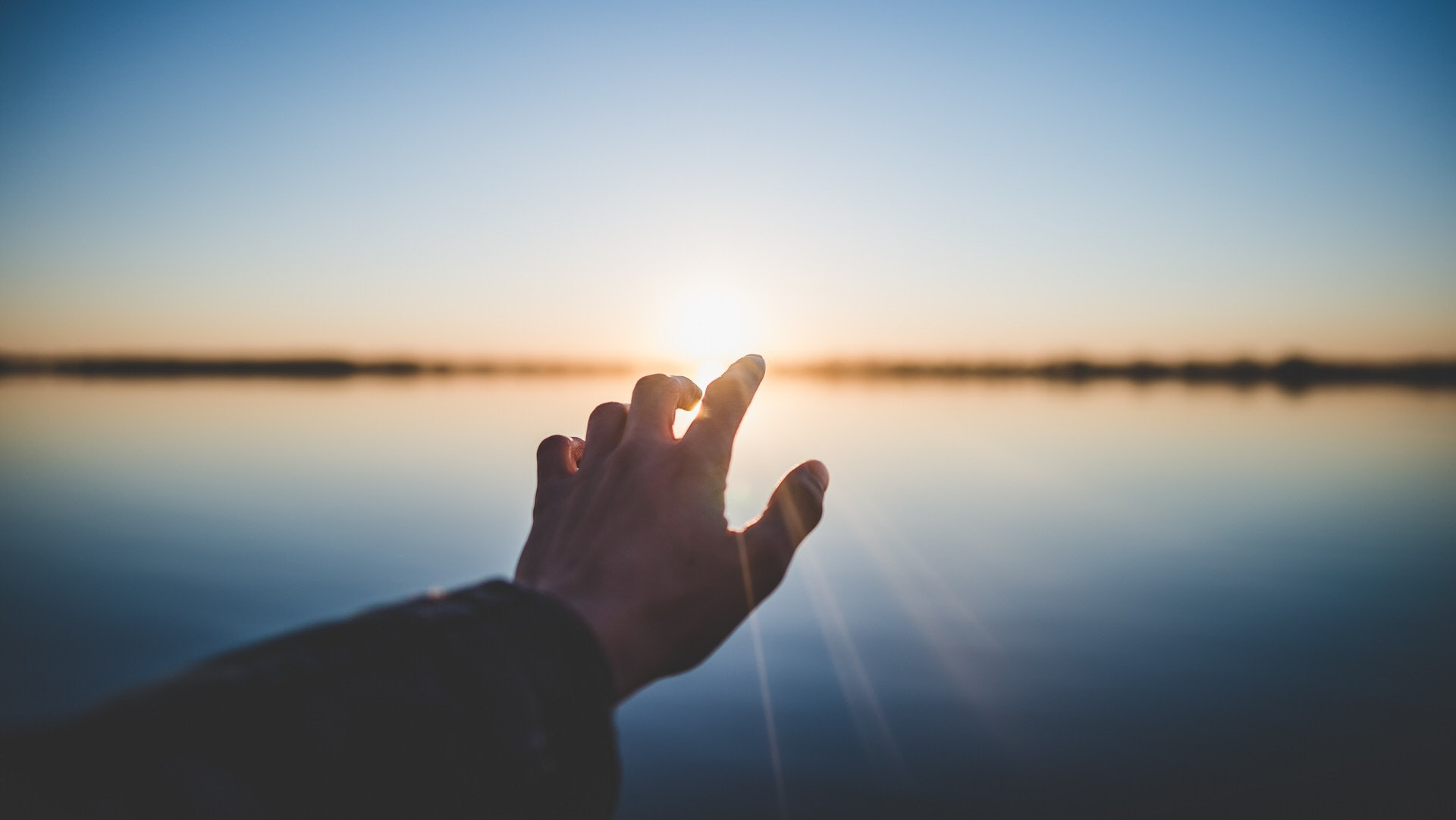 person extending their hand toward the sun near a body of water.