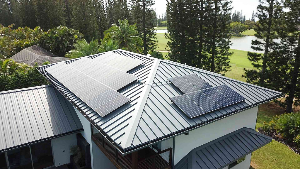 solar panels on a metal roof in Hawaii with pine trees