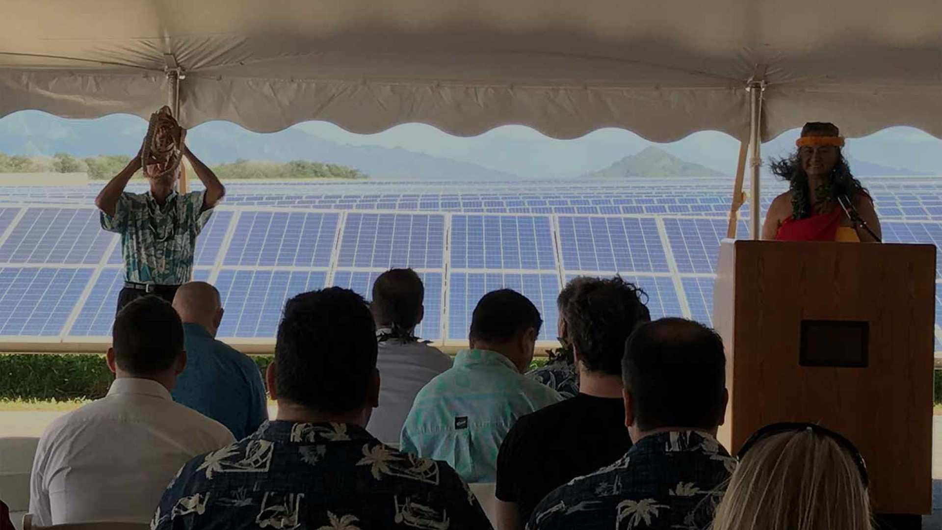 man blowing shell under a tent standing in front of a large solar array