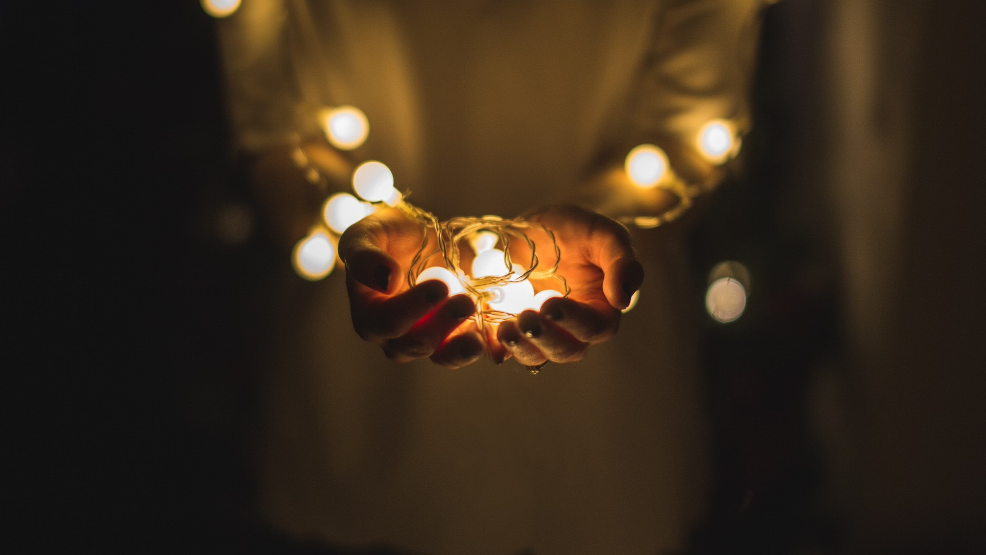 person holding christmas lights in the palm of their hand