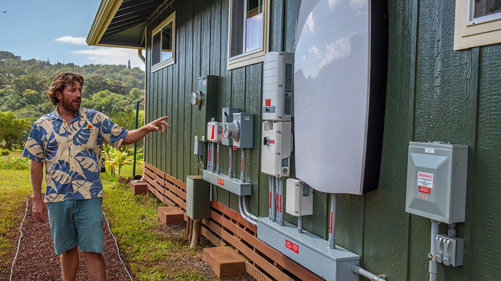 rising sun solar employee showcasing tesla powerwall installed on customer home