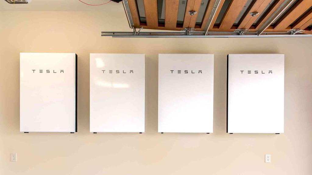 four tesla powerwalls installed on a wall in a Hawaiian home garage