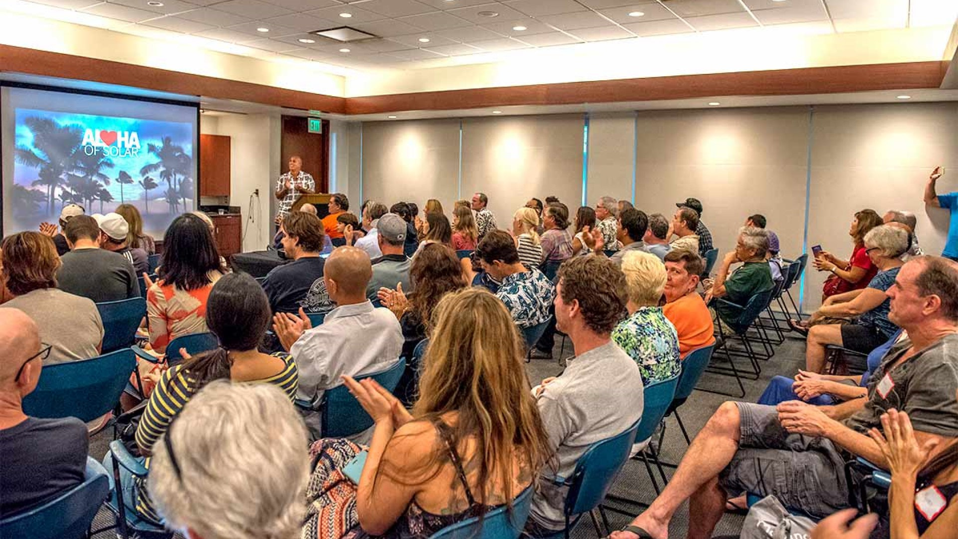 aloha of solar conference put on by rising sun solar. Features people siting in a conference style setting with a projection display